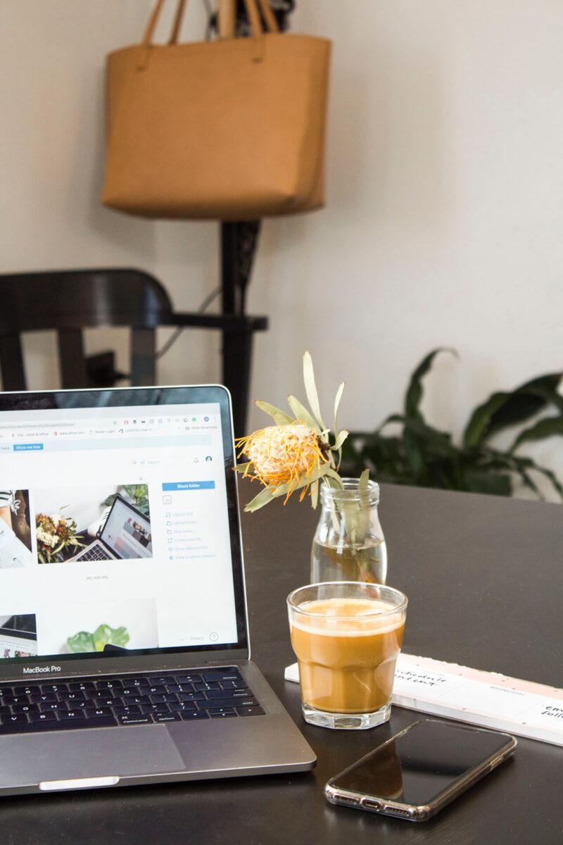 おしゃれなオフィスでMacBookを広げアイスコーヒーを飲みながらWEBマガジン・ブログの記事執筆をおこなう様子
