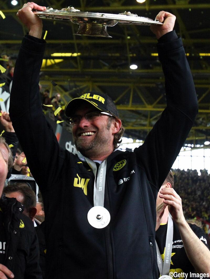 ドイツブンデスリーガでボルシア・ドルトムントを優勝に導き、観客席でマイスターシャーレを掲げてサポーターと喜びあう監督ユルゲン・クロップ
