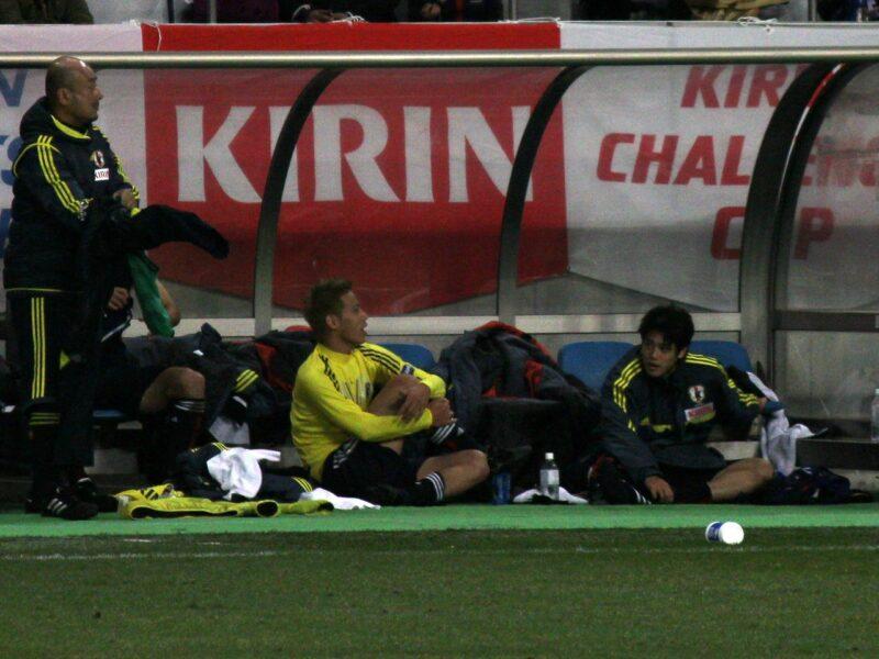 サッカー日本代表チームでの試合で、スタメン出場を終えベンチに下がった後に戦術などについて話し合う本田圭佑と内田篤人