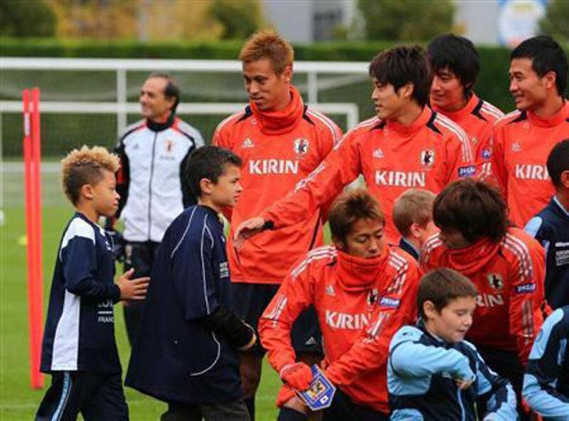 サッカー日本代表チームが海外遠征時に行った現地の子どもたちとの交流で一緒に語らう本田圭佑と内田篤人