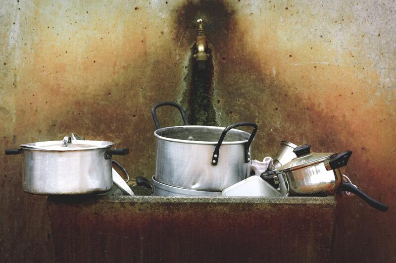 雑然とした様子でシンクに積み重ねられた、洗う前の鍋の山