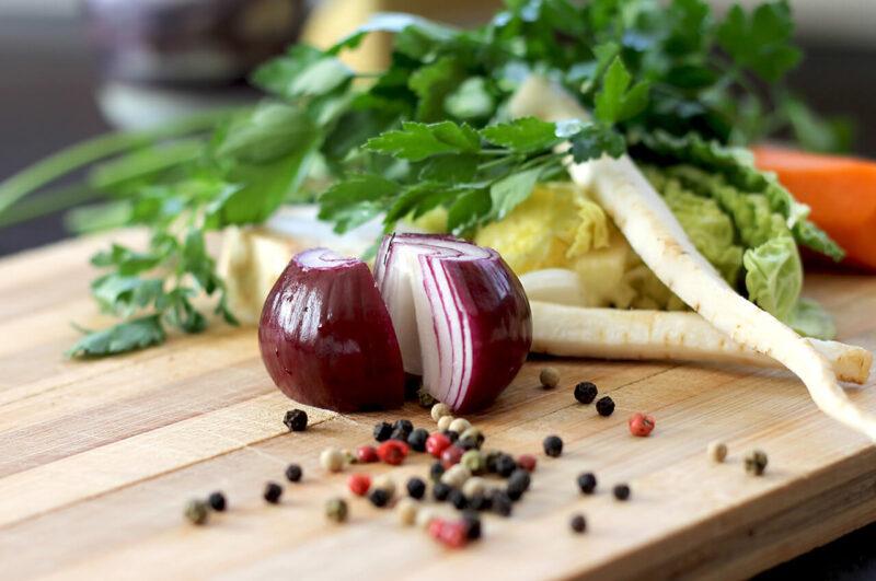 料理に使うためにまな板の上でカットされた玉ねぎなど新鮮な野菜類