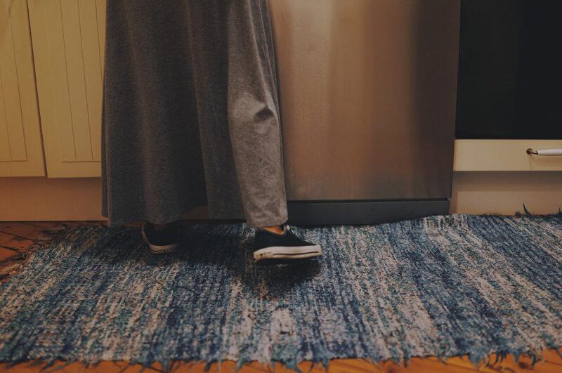 キッチンで料理をつくる女性の足元と、ブルー系のおしゃれなキッチンマット