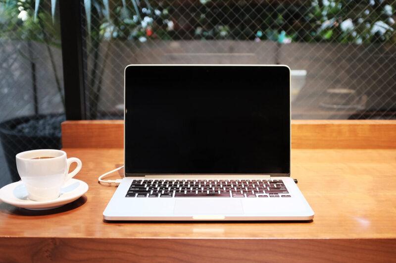 おしゃれなカフェの窓側の席でコーヒーとともにMacBookでブログ・WEBマガジン・アフィリエイトサイト・WEBサイトの記事執筆やデザインをおこなうテーブルの光景