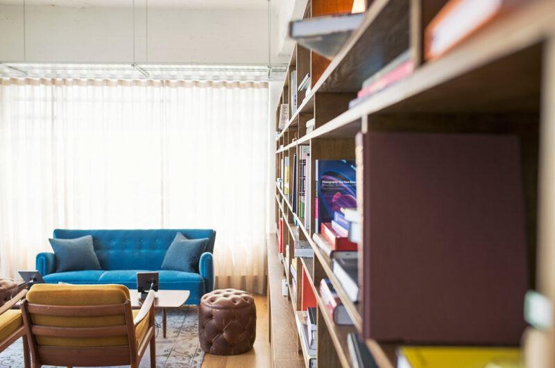 ターコイズブルーとマスタードのソファー、無垢材のテーブルと、天井までの造り付け棚に本や雑貨が並べられた、おしゃれなリビングの光景