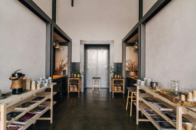 無垢材の棚に並べられたグラスやカップなどの食器とおしゃれな雑誌と、その奥にキッチンが備えられたカフェの光景