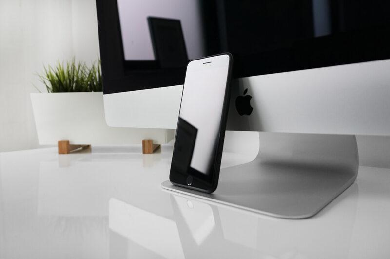 iMacのモニターとiPhoneが置かれた真っ白なデスク