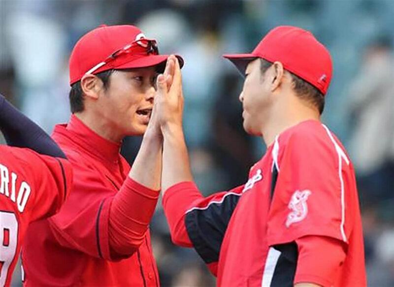 広島カープでの登板試合に勝利し、試合後に先発投手としてチームメイトを迎え入れる黒田博樹と勝利のハイタッチをする新井貴浩