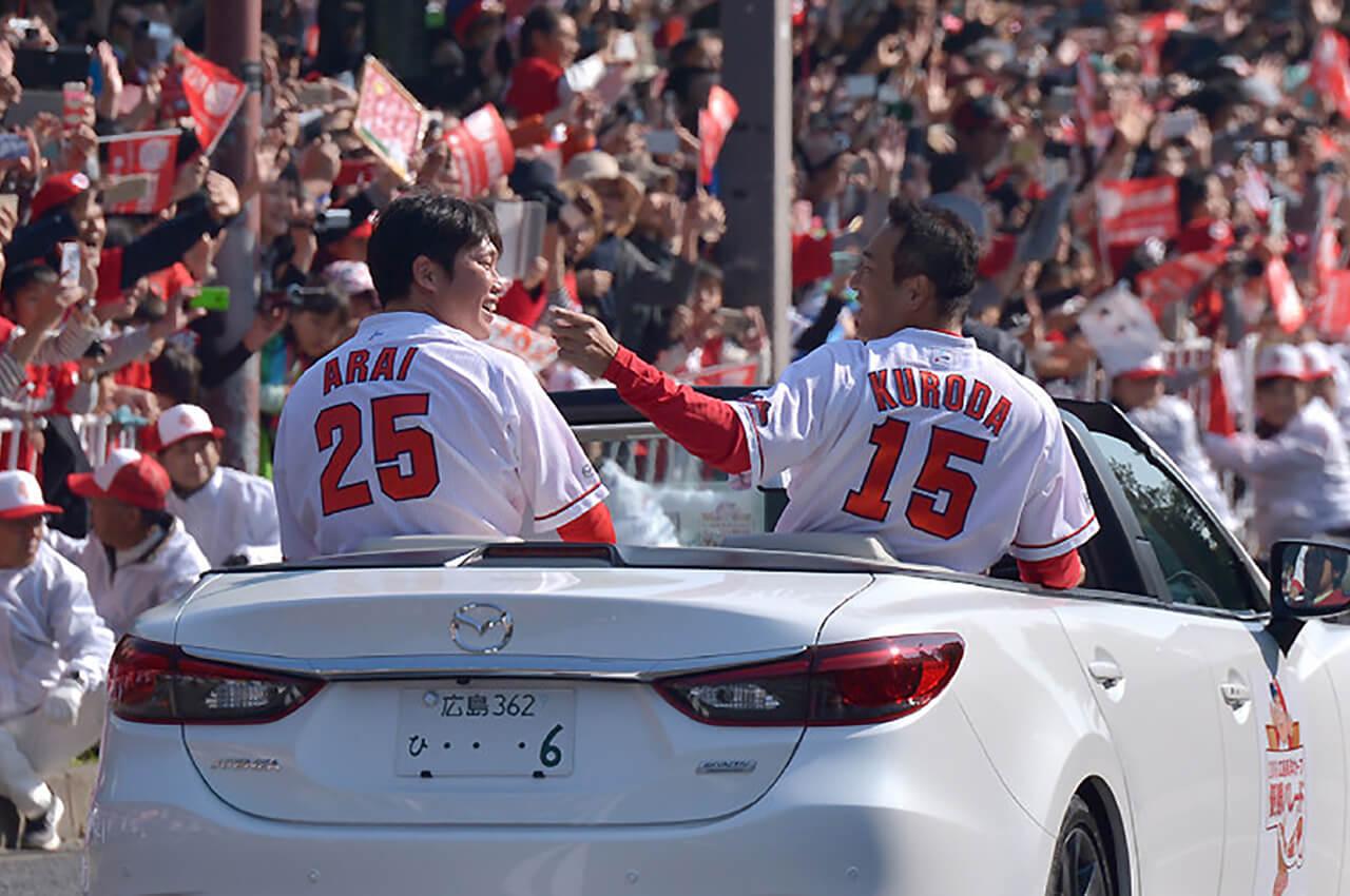 2016年シーズンのリーグ優勝を果たし引退したオフシーズンに広島市内で行われた優勝記念パレードにて、沿道のファンに手をふる広島カープの黒田博樹と新井貴浩