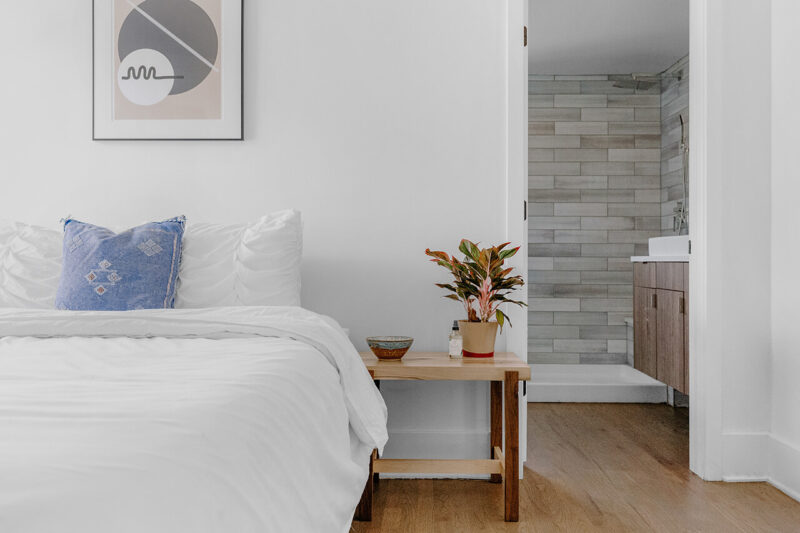 毛穴レスのうるおいたっぷりの綺麗な美肌になるために効果的な、質の良い睡眠をとるためのベッドとベッドサイドテーブルが置かれたおしゃれな寝室