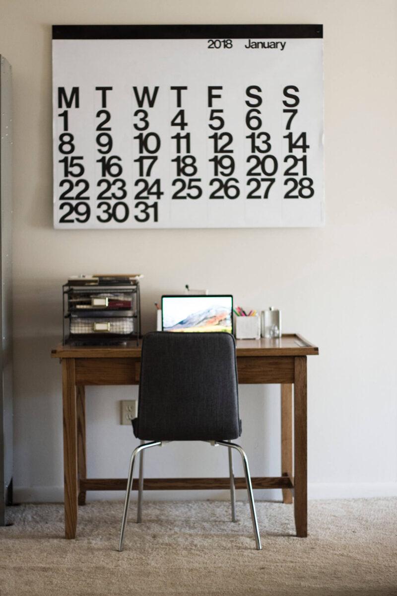 テレワーク(リモートワーク・在宅ワーク)のために自宅で仕事をおこなうためのデスク・椅子とノートパソコン、壁に貼ったスケジュール確認のための大きなカレンダー