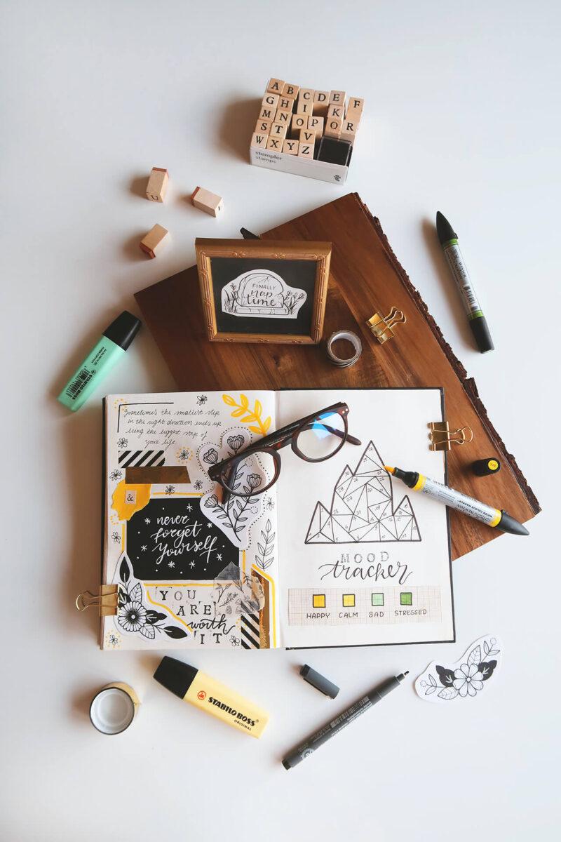 趣味と仕事の息抜きのバレットジャーナルを書くためのお気に入りの輸入ノートブックとペン、眼鏡とフォトフレーム