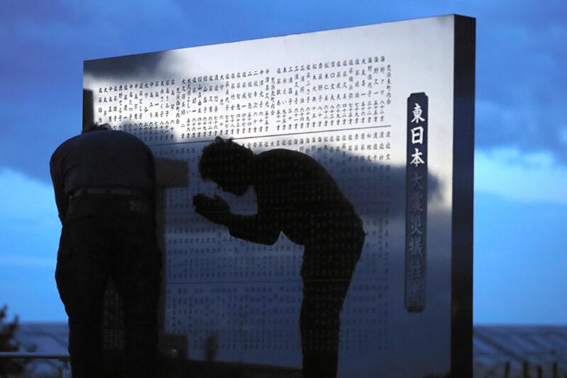 東日本大震災発生から9年経過した2020年3月11日、荒浜海岸近くにある東日本大震災犠牲者の名前が刻まれている碑に手を合わせる男性