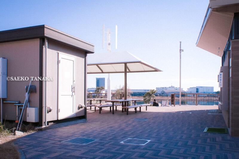 満開のソメイヨシノなどが楽しめる東京の桜名所、大森ふるさとの浜辺公園にあるガラス張りレストハウスの屋外テラス席と、足洗い場と更衣室・シャワー室入口