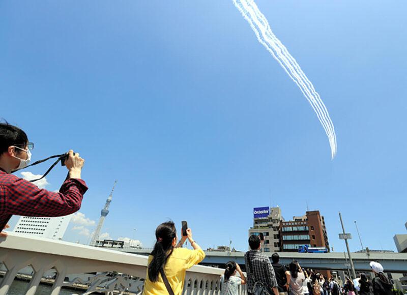 新型コロナウイルス感染症に対応中の医療従事者と多くの国民に感謝と激励を伝えるため、東京の都心上空で編隊飛行をおこなった航空自衛隊のブルーインパルスを見上げる民間の人々