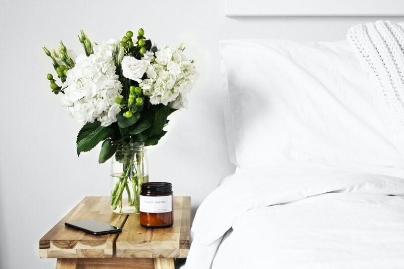 清潔感あふれるベッドサイドのサイドテーブルに飾られた白い花とスキンケア用品