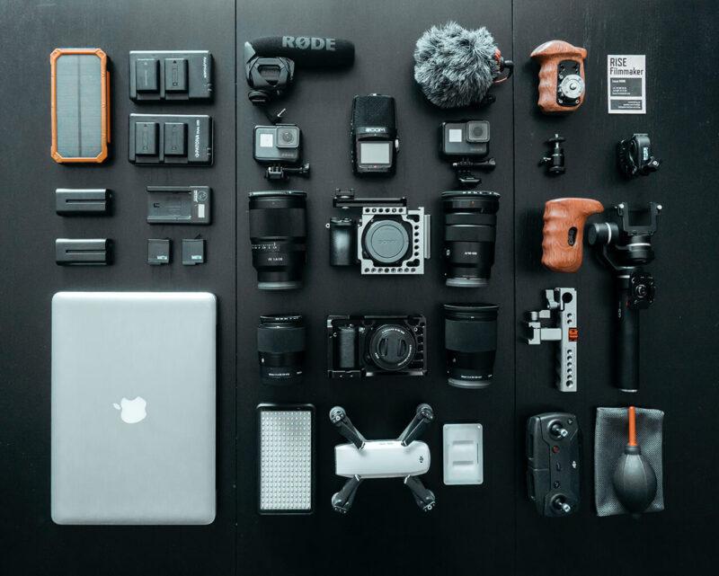 MacBookと一眼レフデジタルカメラのレンズやアクセサリーが並べられた様子