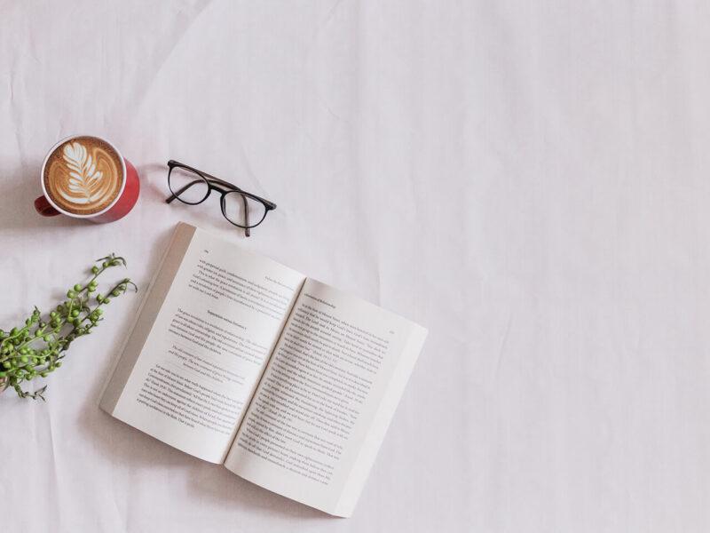 読みかけの本とメガネとラテアートが施されたカフェラテ