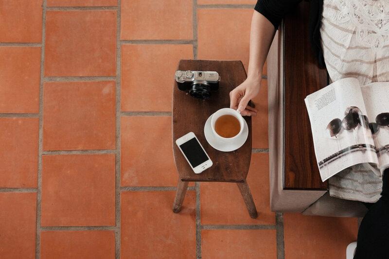 30代40代50代を中心に人気が高いライフスタイル系雑誌を読みながら、サイドテーブルのiPhone・一眼レフカメラの近くに置かれた紅茶を手にする女性の様子