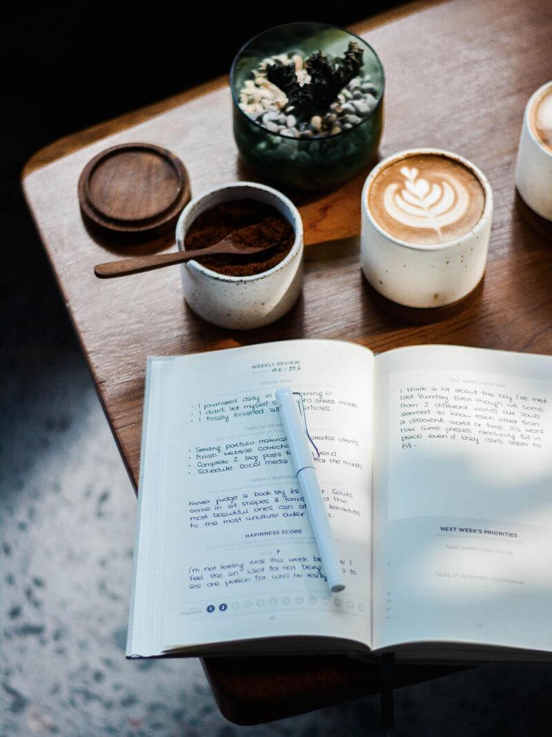 お気に入りのカフェラテとともに、スケジュールや戦略立案、プランニング、アイデアメモを手帳に書き込んでいく仕事風景