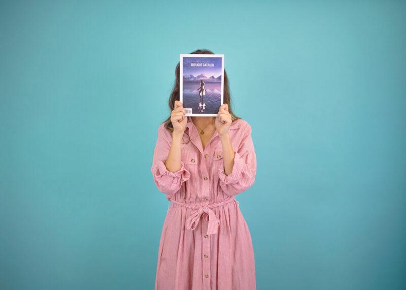お気に入りの雑誌で自分の顔を隠して写真撮影に応じる女性
