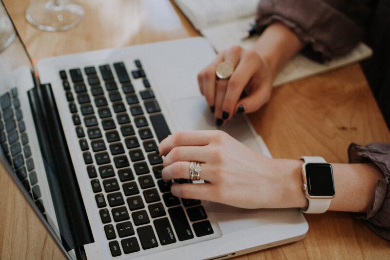 MacBookで顧客のデータを確認しながら提案するプランニング作成とWEBマガジン・ブログの記事執筆を行う女性営業マン