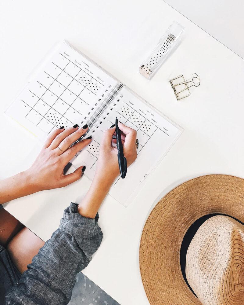 夏の仕事のスケジュールとバカンスの予定を手帳に書き込む女性営業マン