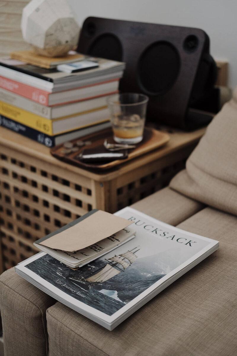 ソファーとテーブルに無造作に置かれた手帳と雑誌の山