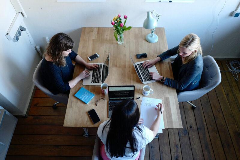 綺麗な花が飾られたおしゃれな会議室にて、MacBookと資料を広げながら顧客へのプレゼンの打ち合わせを行う3人の女性営業マン