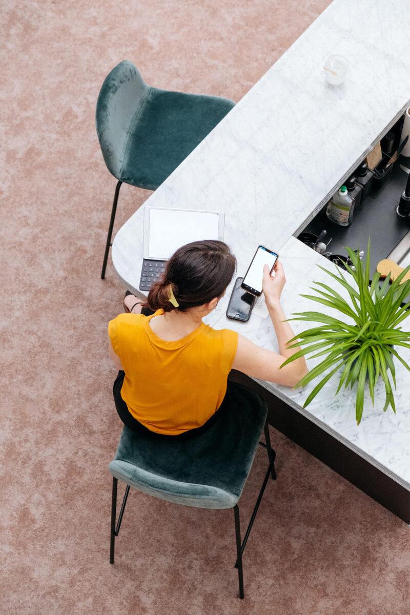 カフェにてMacBookとiPhoneで顧客のデータを確認しながら提案するプランニング作成とWEBマガジン・ブログの記事執筆を行う女性営業マン
