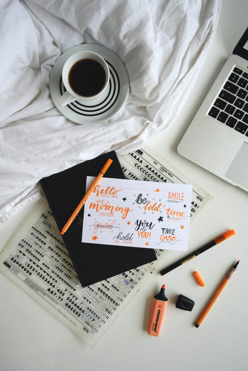 MacBookとコーヒーとともに、ハンドレタリングやコラージュ、イラスト、スケジュール管理、アイデアメモ、日記を手帳に記入する様子