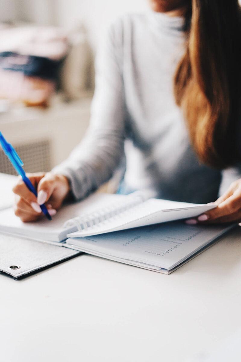 愛用のノートと手帳を広げて、担当するWEBマガジン・ブログのコンテンツプランニングをおこなう女性営業マンの仕事風景
