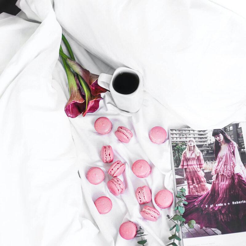 仕事中のテーブルの上に広げたお気に入りの女性ファッション雑誌とマカロン、コーヒーと綺麗な赤い花