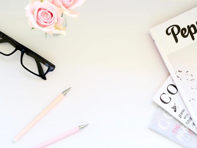 テーブルの上に広げたお気に入りの雑誌とペンとメガネ、そして綺麗なピンクの花