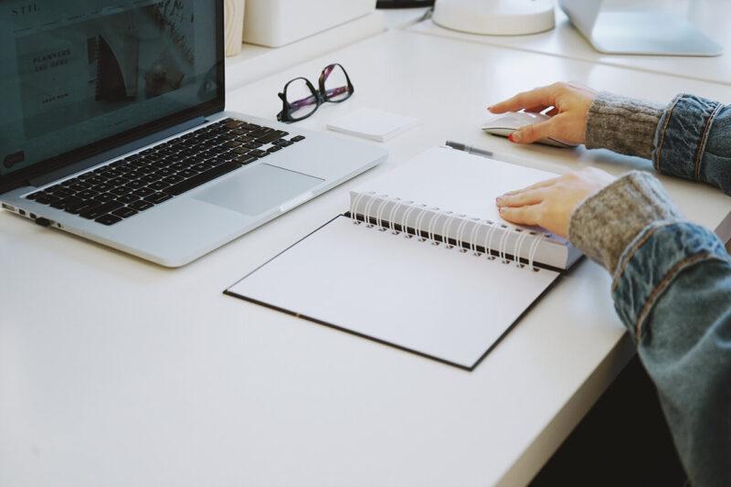 MacBookと手帳で顧客のデータを確認しながら提案するプランニング作成とWEBマガジン・ブログの記事執筆を行う女性営業マン