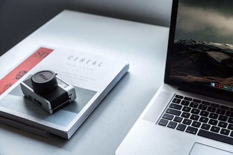 テーブルの上にMacBookと雑誌と一眼レフデジタルカメラを広げた様子