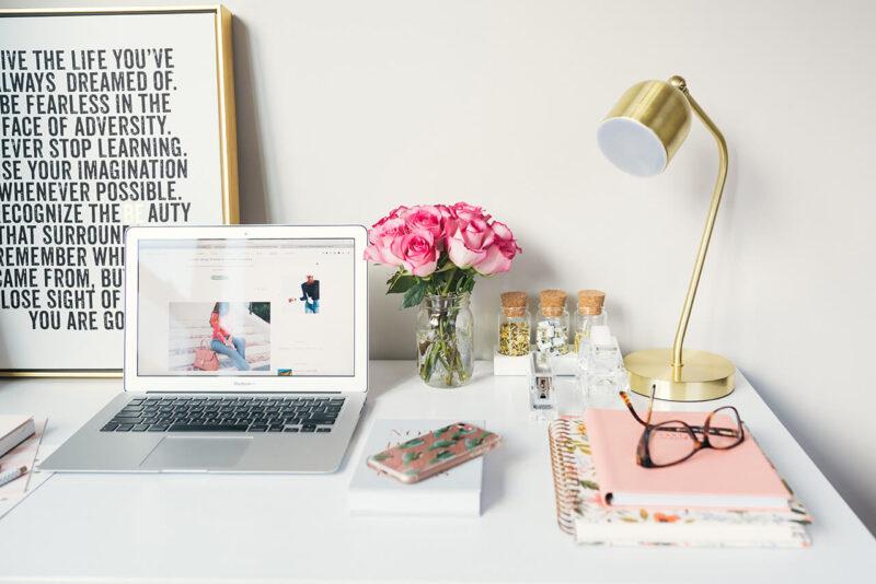 MacBookとiPhone、手帳、雑誌、メガネが置かれ、綺麗なピンクの花が飾られたおしゃれなデスクの風景
