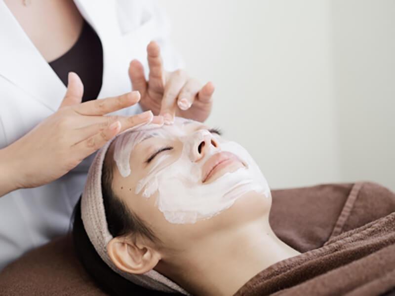 毛穴詰まり・毛穴開き・黒ずみ・角栓・たるみ毛穴・くすみ・ハリ不足・シワを解消する、毛穴レスの美肌に効果的なクレンジング方法を用いたエステでフェイシャル施術を受ける女性