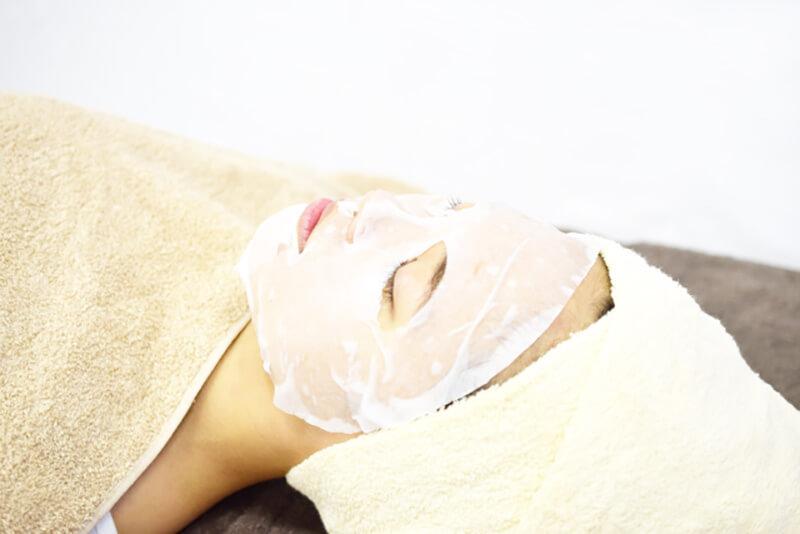 毛穴詰まり・毛穴開き・黒ずみ・角栓・たるみ毛穴・くすみ・ハリ不足・シワを解消する、毛穴レスの美肌に効果的な化粧水の使い方に適した化粧水を使用したエステでのローションパックの施術を受ける女性