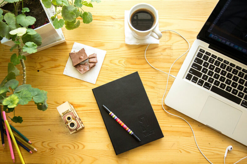 WEBマガジン・ブログの記事執筆のために、コーヒーとクッキーとともに、手帳・MacBook・ペンを広げているデスクの上