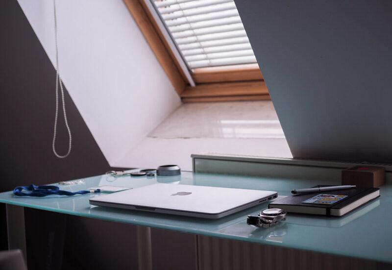 WEBマガジン・ブログの記事執筆のために、大きく開かれた窓の前におかれたデスクにMacBookを広げる様子