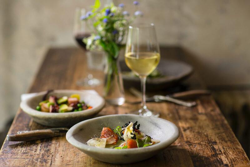 冷えた白ワインと美味しい料理、綺麗な花がダイニングテーブルに並んだ夜ごはん