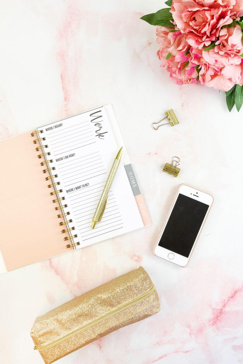 コスメ・美容コンテンツの記事執筆のために手帳とiPhoneを開いて構成を考えるデスクの様子