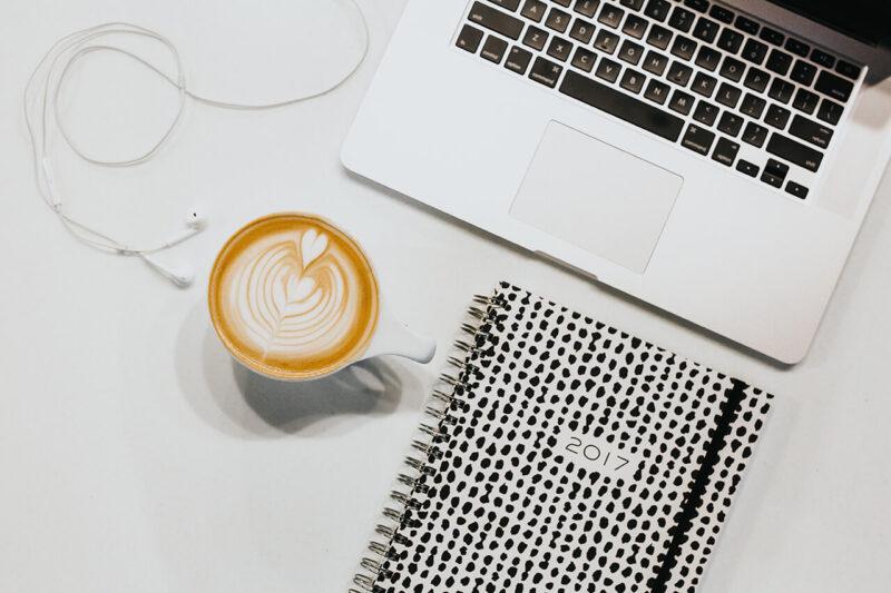 コスメ・美容コンテンツの記事執筆のために手帳とMacBookを開き、カフェラテとともに構成を考えるデスクの様子