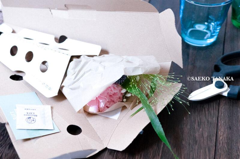 インスタグラムで話題のポストに届くお花の定期便サービス『Bloomee LIFE/ブルーミーライフ』レギュラープラン・2020年7月3日号のお花が入った梱包専用箱を開けた様子と、ショップカードと青山フラワーマーケットの花切りばさみ(フラワーシザー)