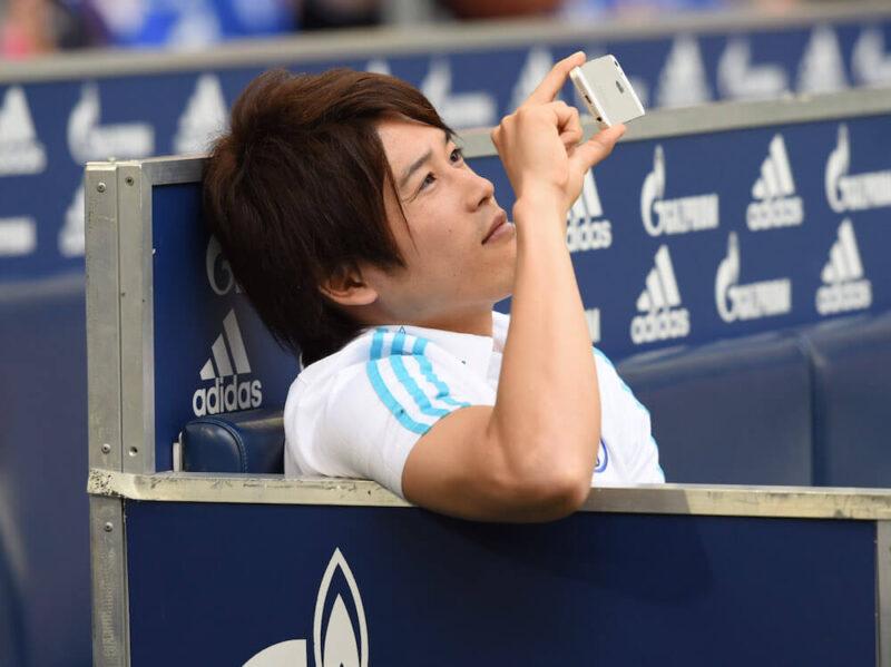 ドイツブンデスリーガのシャルケの公式戦出場前にベンチでカメラ片手にくつろぐ右サイドバック・DFの内田篤人