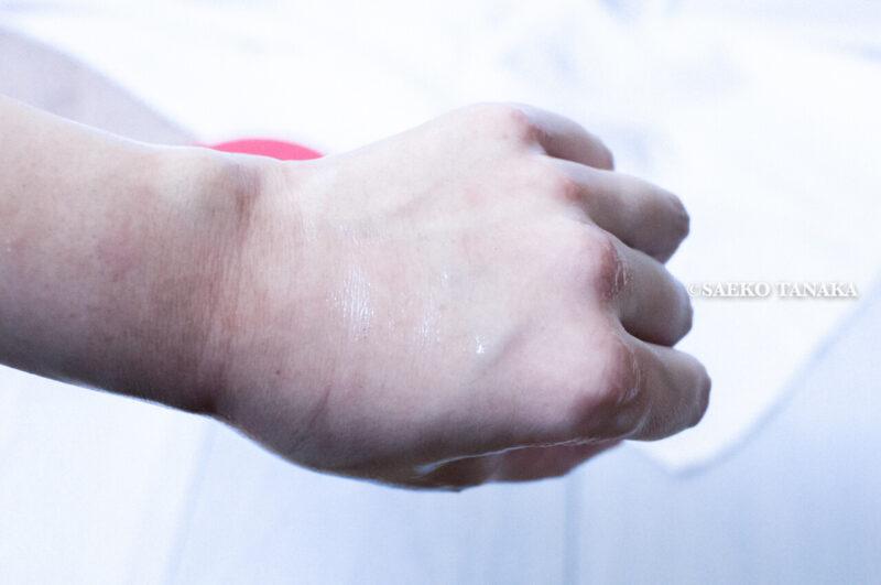 クレンジングしながら肌を保湿・毛穴詰まりの角栓や古い角質を落とす・エイジングケアする効果が期待できる保湿クレンジングクリームとして人気の高いポンズ『エイジビューティークリームクレンジング』をメイクアップ化粧品を乗せた手の甲に乗せてオイル化させた写真