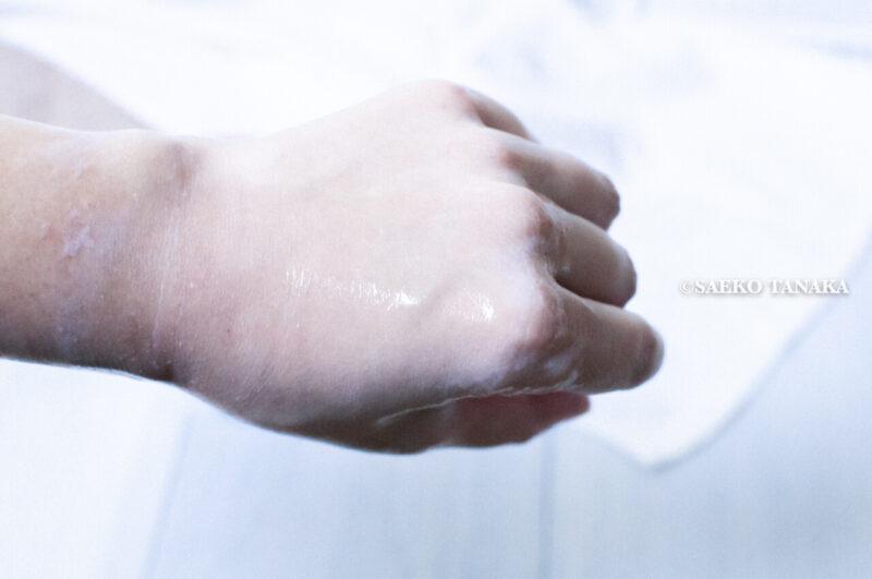 クレンジングしながら肌を保湿・毛穴詰まりの角栓や古い角質を落とす・エイジングケアする効果が期待できる保湿クレンジングクリームとして人気の高いポンズ『エイジビューティークリームクレンジング』をメイクアップ化粧品を乗せた手の甲に乗せて乳化させた写真