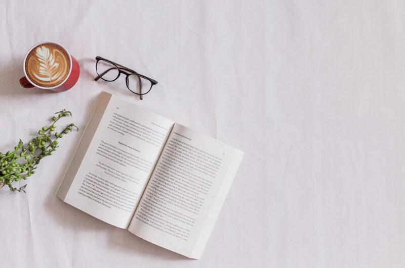 年末年始に巣ごもりで楽しむおうち時間におすすめの本とメガネを広げ、カフェオレを楽しむ