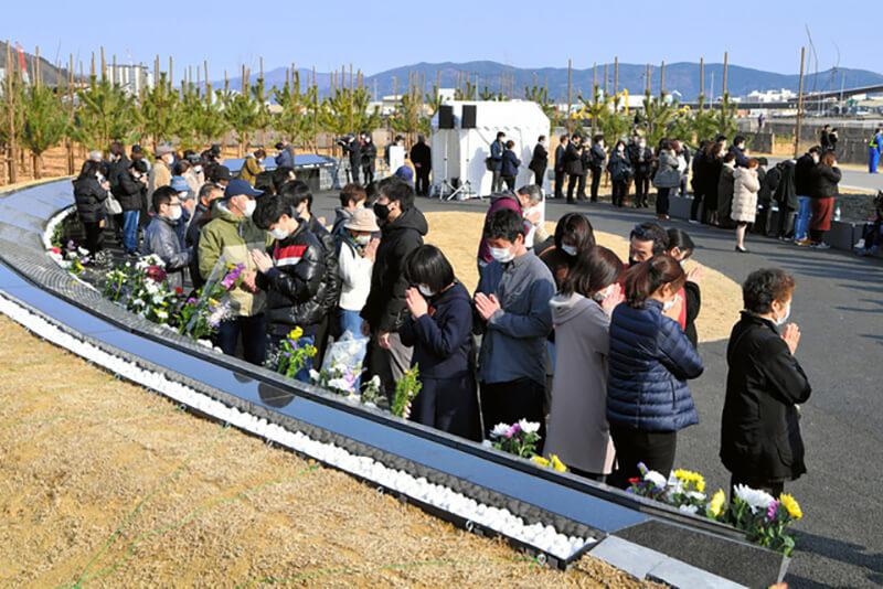 2021年3月11日午前11時44分。宮城県石巻市の石巻南浜津波復興祈念公園にて、命を落とした市民ら3695人の名前を刻んだ慰霊碑の除幕式で、参列した多くの人が刻銘された名前を眺める様子